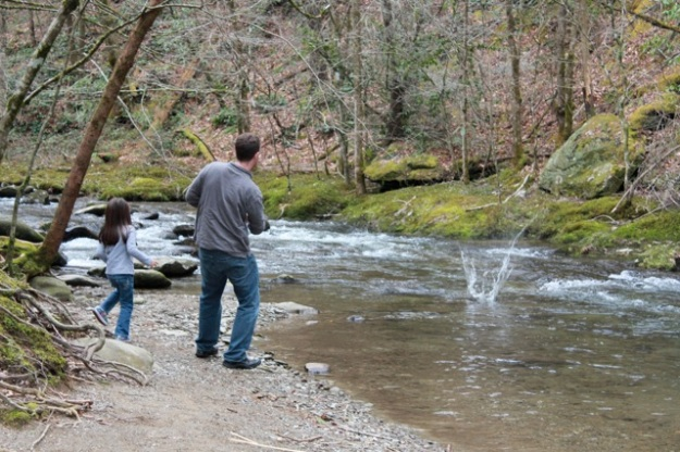 Mia and her daddy having fun skipping rocks on the river.