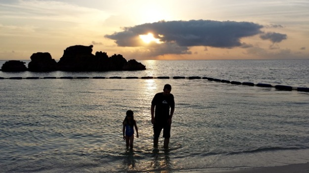Mia and her daddy enjoying some beach time at sunset. — at Araha Beach Okinawa Japan.