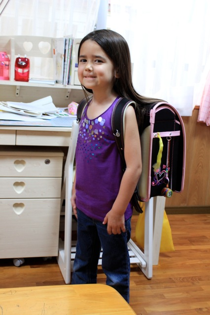 Mia trying on her cousin's cool school backpack.