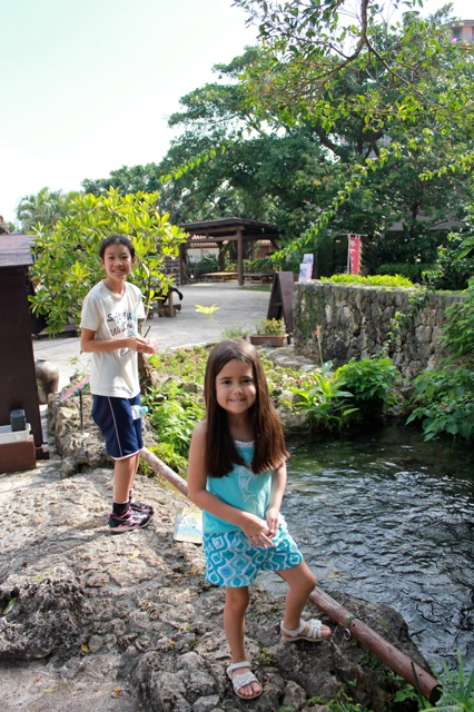 Mia and her cousin feeding Koi fish.