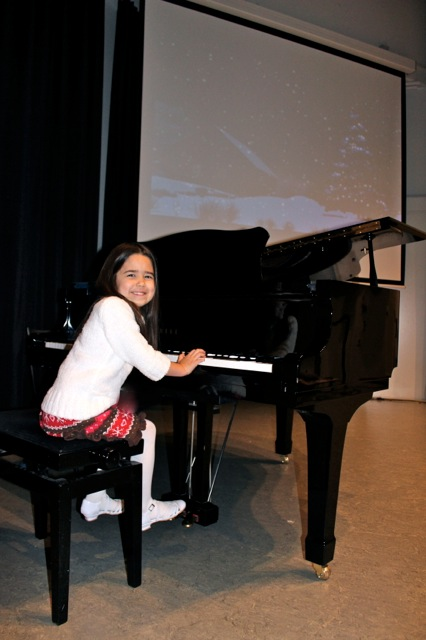 Mia playing the piano at her first piano concert.