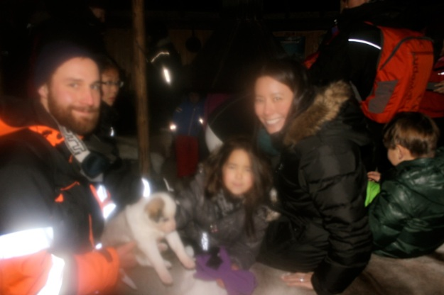 Meeting a cute husky puppy while thawing out by the fire after our sled ride!