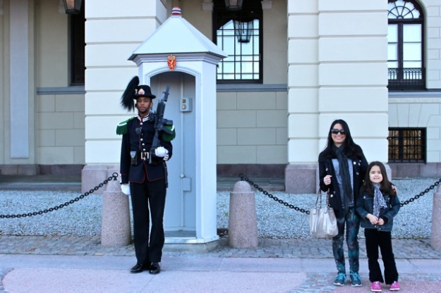 This is Mia and I next to (well as close as we were allowed to get to his circle on the ground) one of the guards in front of the Royal House.