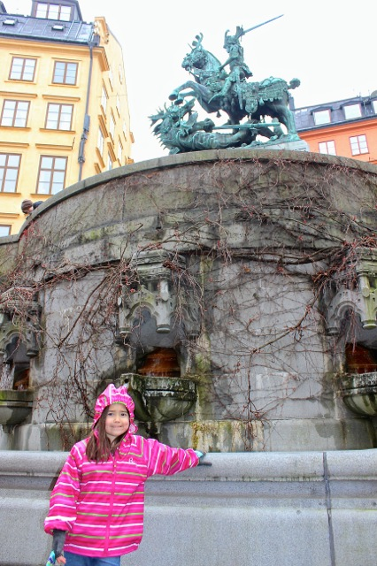 Mia in front of a beautiful water fountain sculpture in Gamla Stan.