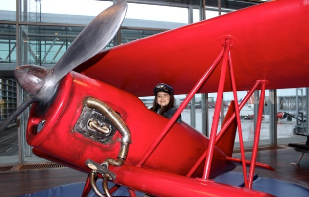 Maybe a future pilot... Mia having fun on a cool red plane at the Stockholm Airport.